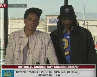 Snoop covers his braids with a Toronto Maple Leafs bucket hat, as his son, Cordell Broadus, speaks about his coming football career at UCLA.