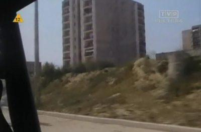 """No, prawie Manhattan. Blok na rogu Belgradzkiej i Braci Wagów, tu jeszcze zasłonięty sporą hałdą. Nie widać więc pawilonu ze sklepem spożywczym PHS na dole, a na górze z wytwórnią dresów Orion. Kadr z serialu TVP """"Dorastanie""""."""