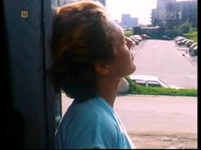 """Pogrążona w przemyśleniach bohaterka filmu, za nią parking przy Symfonii jeszcze nie nadbudowany. Kadr z filmu """"Na Wolność""""."""
