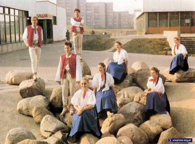 """Zespół tańca ludowego """"Jaromiry"""" pozuje w niecce fontanny na Wiolinowej. Za nimi, po prawej, pierwsza ursynowska restauracja o wyszukanej nazwie """"Ursynowska"""". Zdjęcie z folderu Spółdzielni Jary."""