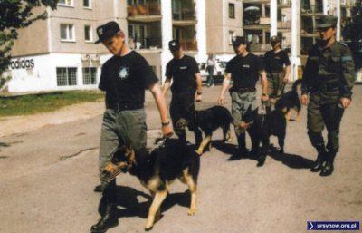 Krok w krok za panami policjantami odzianymi w moro podążają prawdziwe policyjne psy. Amatorzy dresów firmy z lewej (sklep na Cybisa) dali więc drapaka. Cudne lata '90! Zdjęcie z folderu Gminy Ursynów.