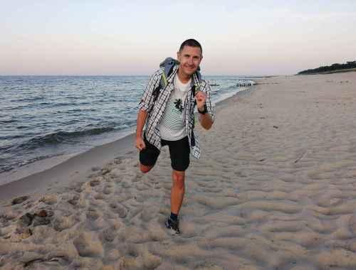 Chłopak z plecakiem biegnie wieczorem po plaży