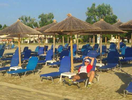 biegacz odpoczywa po treningu na plaży, greckie wakacje