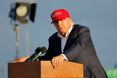donald trump: SAN PEDRO, CA - SEPTEMBER 15, 2015: Donald Trump, 2016 Republican presidential candidate, speaks during a rally aboard the Battleship USS Iowa in San Pedro, Los Angeles, California while wearing a red baseball hat that says campaign slogan Make America G Editorial