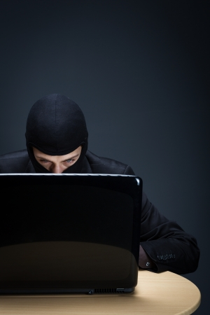 computer ninja: Secretive computer hacker bent closely over a computer screen in the darkness stealing important and private information, conceptual image