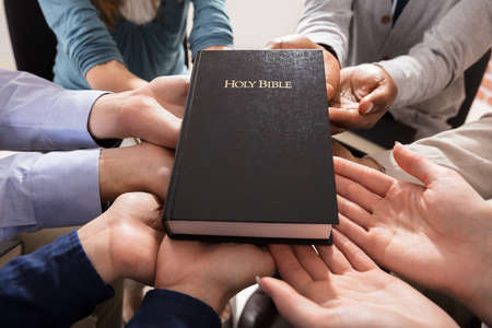 holy people: Holy Bible Over The Hands Of Diverse People