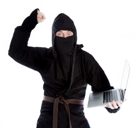 COMPUTER NINJA: Attractive 30 years old caucasion man shot in studio isolated on a white background Stock Photo