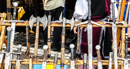 weapon racks: Medieval axe, swords and ather weapons on a wodden rack, at a Medieval festival in Brasov