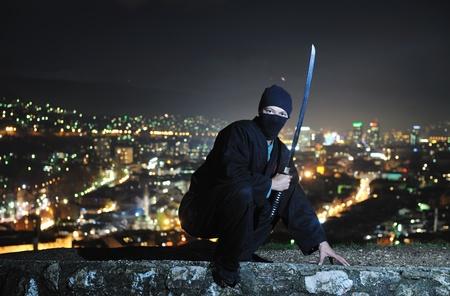 ninja: ninja hold katana samurai old martial weapon sword at night with city lights in background