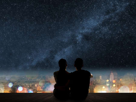 couple in love staring: Silhouette of young Asian couple sit on wooden ground above the city under stars. Stock Photo