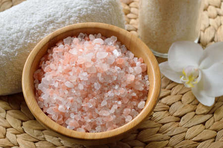 Pink salt from the Himalaya. Closeup of pink SPA salt in wooden bowl with orchid flower and towel. Stock Photo - 17815252