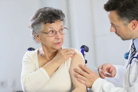 Doctor doing vaccine injection to elderly woman Stok Fotoğraf - 34972689