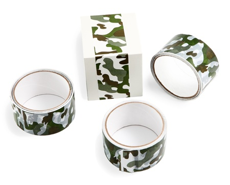 Three rolls of duct tape with print green camouflage and a box wrapped with ribbon for packing purchases and gifts. Flexible packaging materials and products. Stock Photo - 20231158
