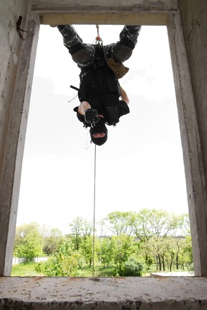 Photo of armed man in combat uniform playing terrorist or special forces team member hanging head down on the rope Stock Photo - 9790189