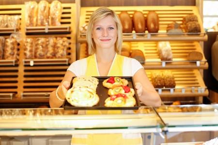 baguette de pain: Commerçant en boulangerie présente une tablette pleine de gâteaux
