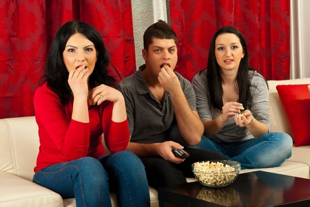 Three people sitting on couch watching tv at sad movie and eating popcorns Stock Photo - 13081117