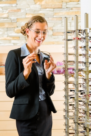 Young woman at optician with glasses, she might be customer or salesperson Stock Photo - 19000725