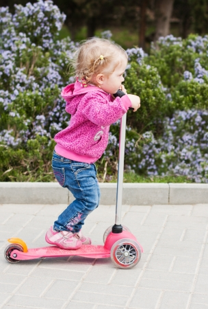 toddler girl on a scooter in a park in spring day photo