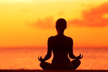 Zen yoga woman doing meditation on beach - wellness concept. Female silhouette relaxing sitting at sunset background meditating at ocean retreat. Summer orange sunrise sky. Stock Photo - 37924086