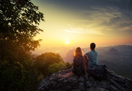 dawn: Two hikers on top of the mountain enjoying sunrise over the tropical valley