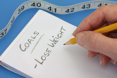 Making a note to lose weight, after unpleasant results with the tape measure Stock Photo - 42781008