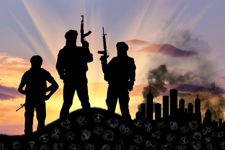 war death: Concept of a terrorist attack. Silhouette of terrorists with a rifle standing on a pile of skulls on the background of the city in smoke