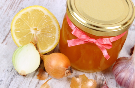 honey garlic: Fresh organic honey in glass jar, onion, garlic and lemon on old wooden background, healthy nutrition, strengthening immunity and treatment of flu