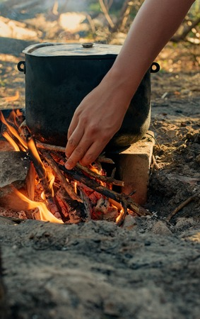 survival equipment: Tourist kettle on camp fire. hand with firewood Stock Photo