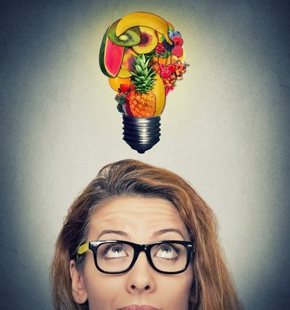 Manger idée et conseils sur l'alimentation saine conception. Gros plan portrait headshot femme regardant ampoule plodovo dessus de la tête sur le mur gris de fond. Banque d'images - 45042561