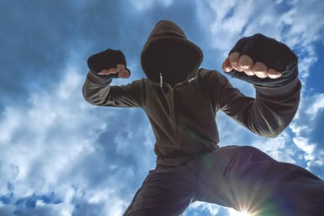 Ataque violento, irreconocible penal Varón encapuchado víctima patadas y puñetazos en la calle. Foto de archivo - 54381936