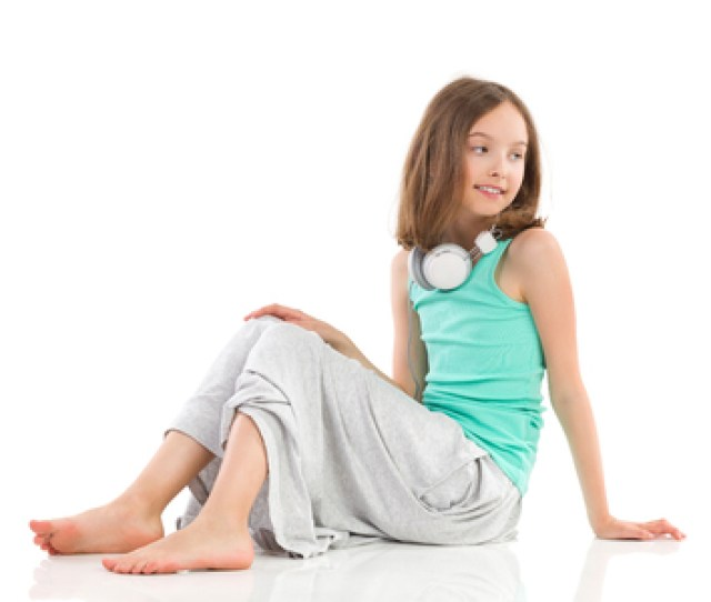 Young Girl With Headphones On Her Neck Is Sitting On The Floor And Looking Away