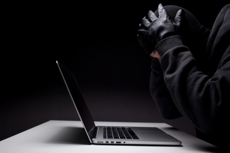 COMPUTER NINJA: Computer hacker in a balaclava working in the darkness stealing data and personal identity information off a laptop computer Stock Photo