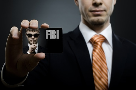 fbi: secret agent in black costume and orange necktie reach out on camera and show visiting card, close up