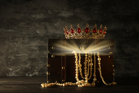 Image of mysterious opened old wooden treasure chest with light and queen/king crown with red Rubies stones. fantasy medieval period. Selective focus. Stock Photo - 99005885