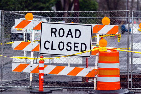 Road closed sign on the white plate,attached to the turnstile with orange and white stripes near the fenced area emergency road conditions Stock Photo - 26143667