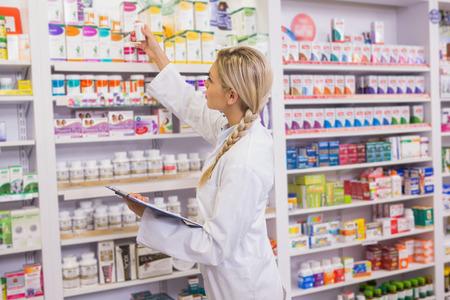 boite médicament: Pharmacien junior prendre des médicaments de l'étagère dans la pharmacie Banque d