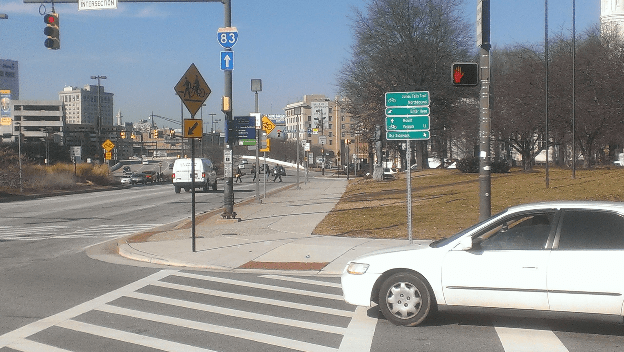 Click to Enlarge. The sign here clearly shows that the sidewalk and crosswalk are designated as bike routes. But a cyclist struck by a truck here is being faulting for riding on the sidewalk. Image: ##http://www.bikemore.net/blog/anti-bicycle-policing-must-stop## Bikemore##