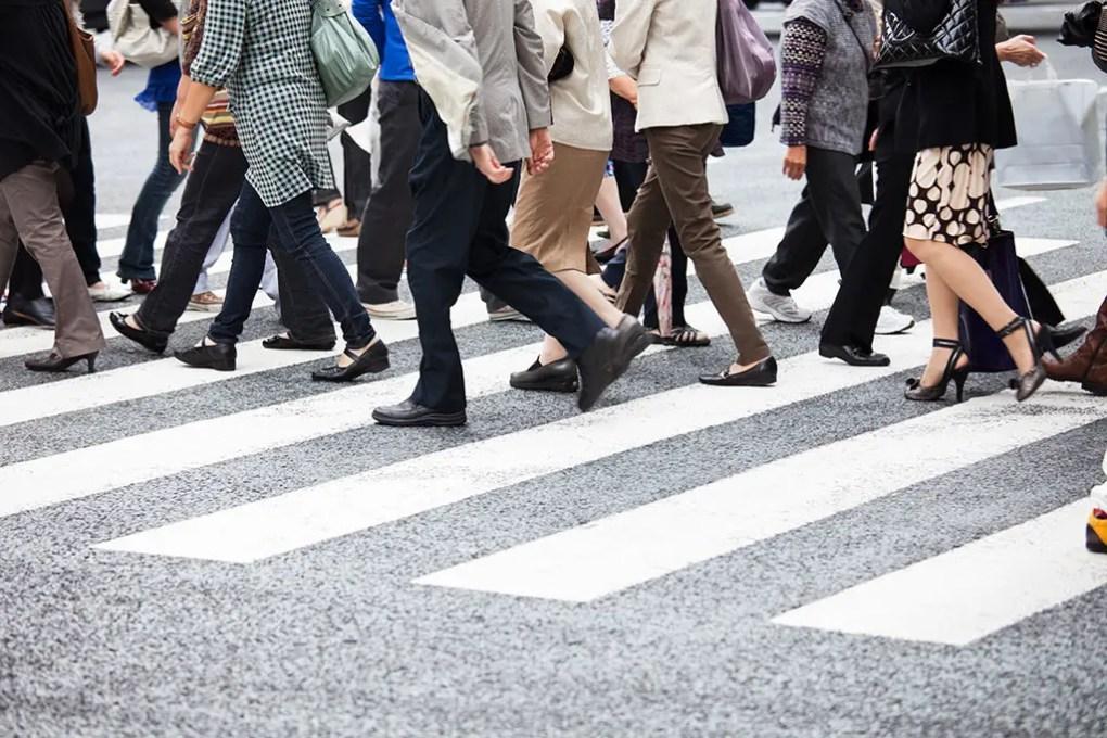 Group of pedestrians walking across a crosswalk. Pedestrian Accident Lawyer.