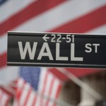 Wall Street Sign with American Flag in Background