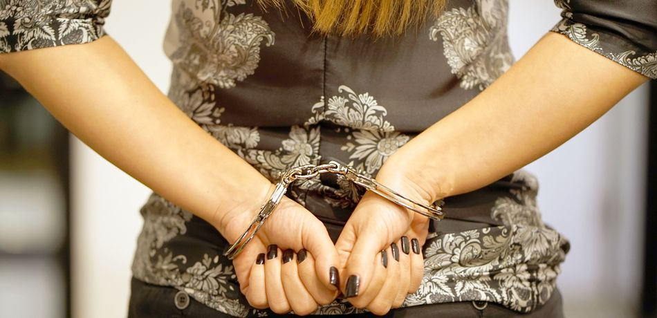 Woman with hands cuffed behind her back.