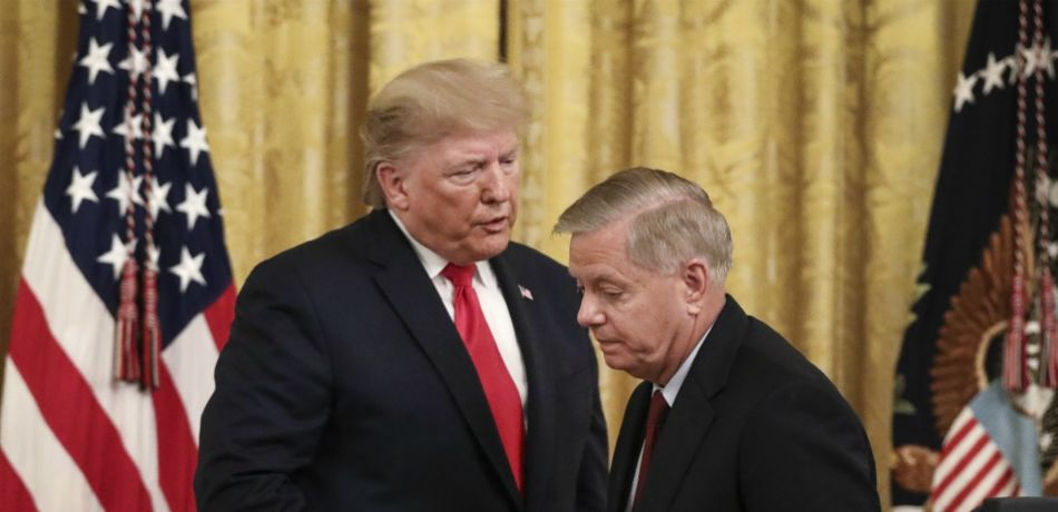 President Donald Trump shakes hands with Sen. Lindsey Graham during an event about judicial confirmations in the East Room of the White House.