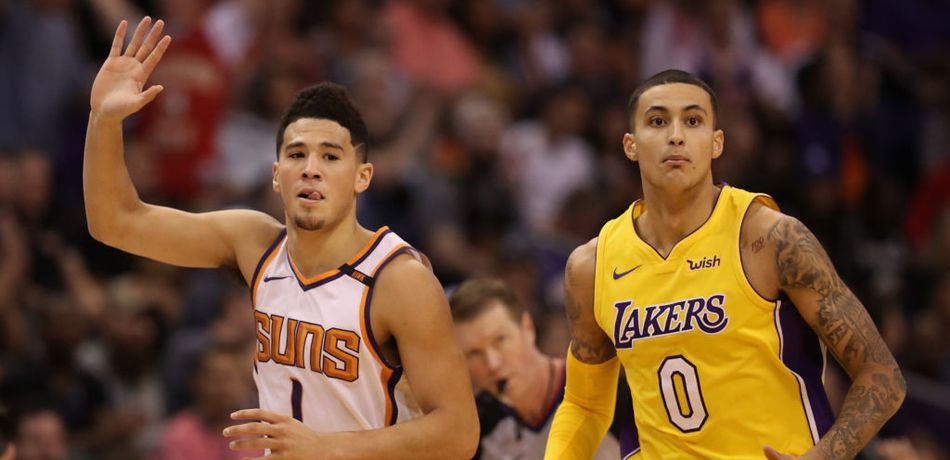 Devin Booker #1 of the Phoenix Suns reacts to a three point shot ahead of Kyle Kuzma #0 of the Los Angeles Lakers during the NBA game at Talking Stick Resort Arena on November 13, 2017 in Phoenix, Arizona.