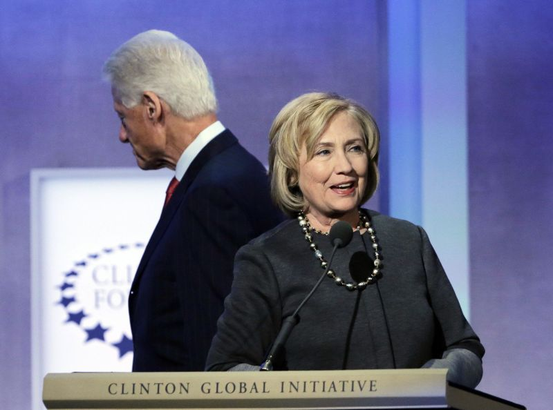 """Former Secretary of State Hillary Rodham Clinton begins to speak at the podium as her husband, former U.S. President Bill Clinton, moves to take a seat on the stage after introducing her at the Clinton Global Initiative, Monday, Sept. 22, 2014, in New York. The session is called """"Reimagining Impact."""" (AP Photo/Mark Lennihan)"""
