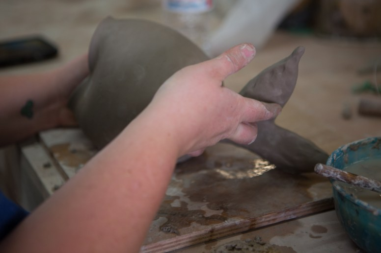 Rachel Hale, potter, creates a fish out of clay at Muddy Evolution in Apalachicola, FL. / ©2017 Audrey Horn / www.usathroughoureyes.com