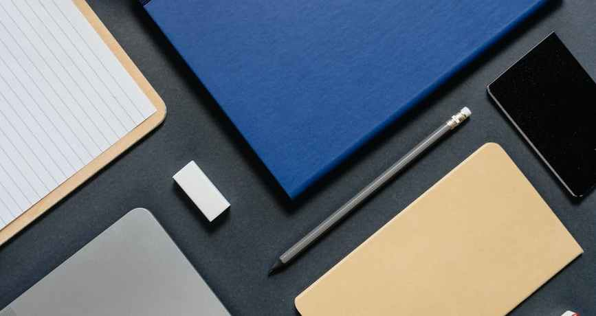 a flatlay of a laptop and office supplies