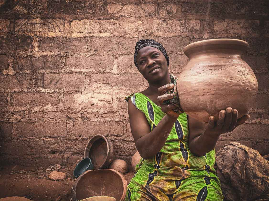 african woman showing handicraft earthenware in local workshop