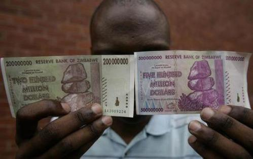 A man holds up d 200 million and 500 million Zimbabwe dollar notes in the capital Harare December 12, 2008.   REUTERS/Philimon Bulawayo