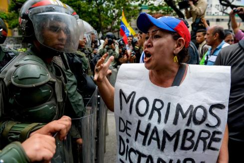 """TOPSHOT - A woman with a sign reading """"We starve"""" protests against new emergency powers decreed this week by President Nicolas Maduro in front of a line of riot policemen in Caracas on May 18, 2016. Public outrage was expected to spill onto the streets of Venezuela Wednesday, with planned nationwide protests marking a new low point in Maduro's unpopular rule. / AFP / FEDERICO PARRA (Photo credit should read FEDERICO PARRA/AFP/Getty Images)"""
