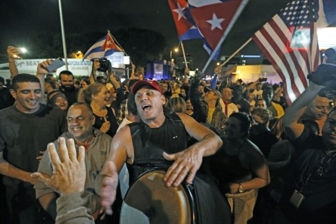 MANDATORY CREDIT People in Miami celebrate the death of Cuba's Fidel Castro in front of Versailles Restaurant in Little Havana, early Saturday, Nov. 26, 2016. Within half an hour of the Cuban government's official announcement that former President Fidel Castro had died, Friday, Nov. 25, 2016, at age 90, Miami's Little Havana teemed with life - and cheers. (Al Diaz/Miami Herald via AP)