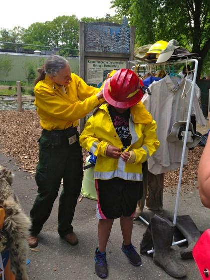 Catherine Hibbard helps Angelo put on the firefighter helmet. Credit: USFWS